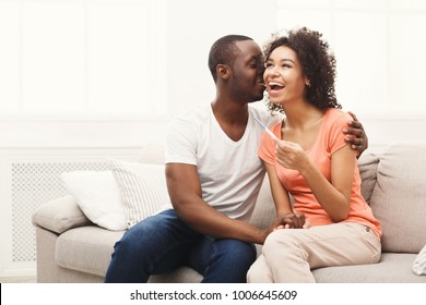 Young balck couple happy about positive results of pregnancy test, hugging and kissing each other, copy space