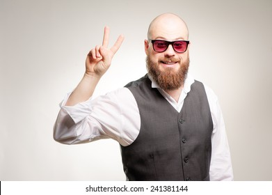 young bald caucasian man with long beard in sunglasses showing the victory gesture while smiling for the camera on white background