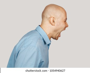 Young bald guy screaming. Side view. Isolated on gray background.