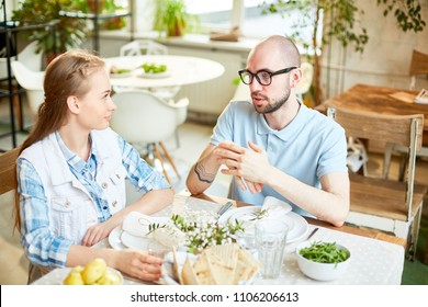 Young bald male in glasses and female sitting at served table looking to each other and chatting in cafe