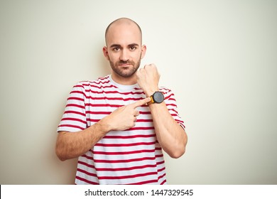 Young bald man with beard wearing casual striped red t-shirt over white isolated background In hurry pointing to watch time, impatience, looking at the camera with relaxed expression
