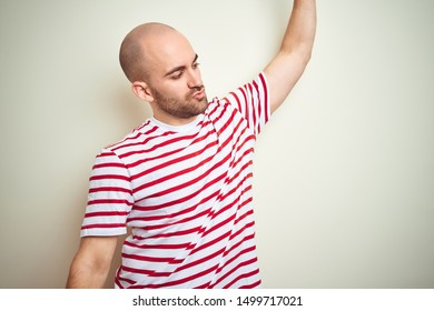 Young bald man with beard wearing casual striped red t-shirt over white isolated background Dancing happy and cheerful, smiling moving casual and confident listening to music