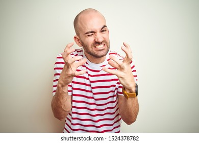 Young bald man with beard wearing casual striped red t-shirt over white isolated background Shouting frustrated with rage, hands trying to strangle, yelling mad