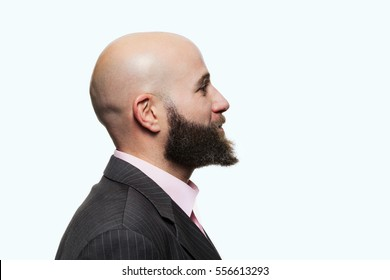 Young bald man with a beard wearing a stylish jacket, side view