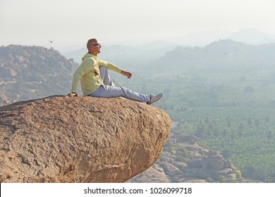 A young bald man sits on top of a mountain against a background of sunrise  or dd4740a49644