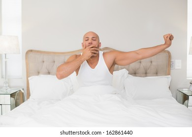 Young bald man waking up in bed and stretching his arms at home