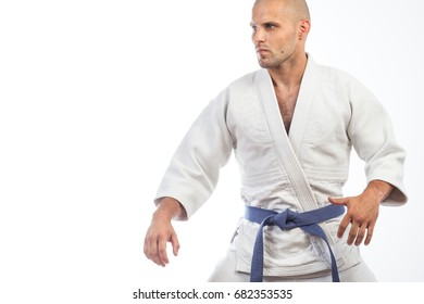 A young bald man in a white kimono and blue belt for a kimono, sambo, jiujitsu stands in a fighting pose on an isolated white background