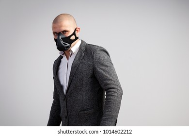A young bald man in a white shirt, gray suit  and black trainig mask confidently looks at the camera and posing on a white isolated background
