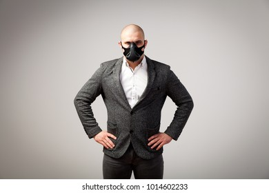 A young bald man in a white shirt, gray suit  and black trainig mask posing on a white isolated background