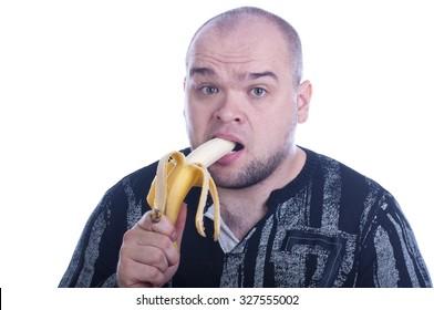 Young bald serious man eats yellow banana isolated white