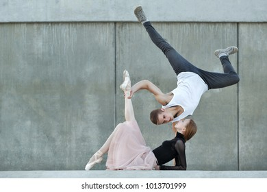 A young ballerina and an athlete parkour dance on the streets of the city. Passion in the dance. An unusual couple in love. Date dancers