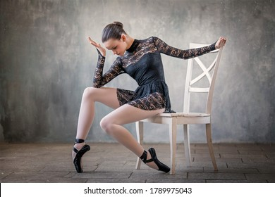 young ballerina in a black suit and black pointe shoes, dancing against the background of a textured wall, froze in a graceful pose sitting on a white chair