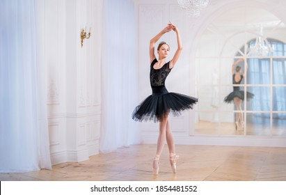 young ballerina in a black tutu is dancing on pointe in a large bright hall in front of a mirror.