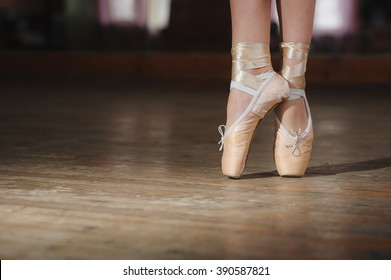Young ballerina or dancer girl dancing, closeup on legs and shoes, standing in pointe position. old wooden floor
