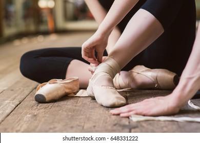 Young ballerina or dancer girl putting on her ballet shoes on the wooden floor. Ballet dancer tying ballet shoes. close-up.