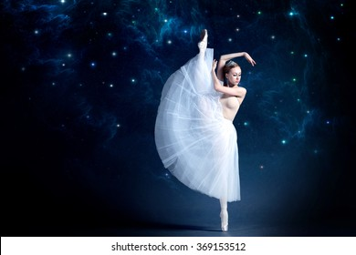 Young ballerina is dancing with the starry night sky in the background. Girl is wearing a beautiful dress that adds a romantic and wondering atmosphere to the photo.