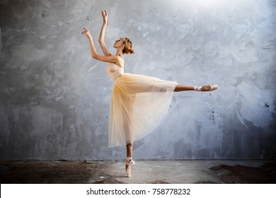 Young ballerina in a golden colored dancing costume is posing in a loft studio