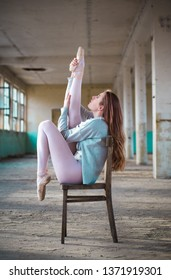 Young ballerina in an old building sitting on the chair with her legs up in the air. Young, elegant, graceful woman ballet dancer