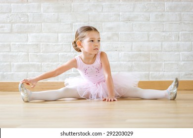 Young ballerina in pink clothes sitting on the floor during the training in dance class.