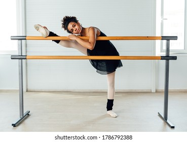 Young ballerina stretching her leg in dance studio. Woman doing exercise on ballet barre.