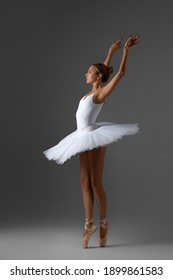 Young ballerina in white tutu and pointe shoes is dancing on studio background