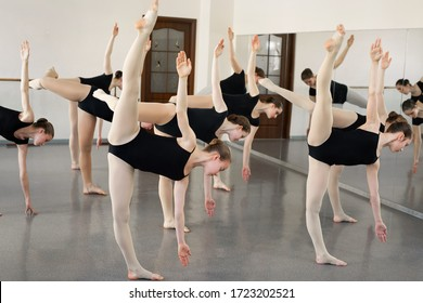 Young ballerinas do complex exercises in ballet school