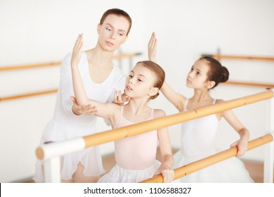 Young ballerinas making position in light clothes with pedagogue in dancing studio