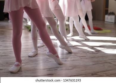young ballerinas training at hall, ballet dancers in pointe shoes rehearse in class and stretching legs