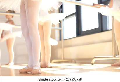 Young ballerinas wearing pointe shoes, the special reinforced satin shoes allowing a ballet dancer to stand on tip toe, low angle view of a class in progress