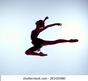 young ballet dancer jumping on a grey background. Ballerina is wearing in blue dress and pointe shoes. The outline shooting - silhouette of girl