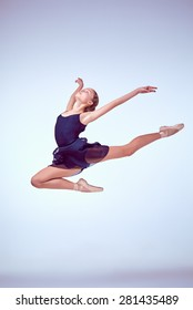 young ballet dancer jumping on a grey background. Ballerina is wearing in blue dress and pointe shoes