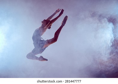 young ballet dancer jumping on a lilac background. Ballerina is wearing in blue dress and pointe shoes. The outline shooting - silhouette of girl with smoke effect