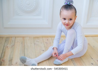Young ballet dancer preparing for lesson sitting on the wooden floor