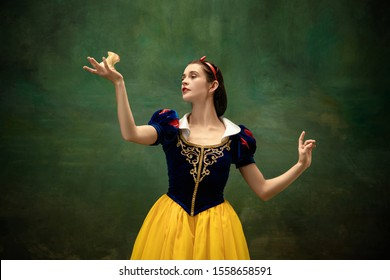 Young ballet dancer as a Snow White with poisoned apple in forest. Flexible caucasian ballerina dances like character of fairytail in bright clothes. Adorable and modern story in emotions. - Shutterstock ID 1558658591