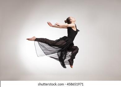 Young ballet dancer wearing black transparent dress jumping
