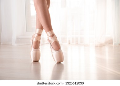 Young ballet dancer wearing pointe shoes indoors
