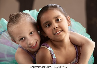 Young ballet student gives her friend a hug