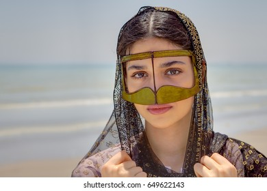 Young bandari woman wearing a traditional mask called the burqa, Coast of the Persian Gulf near the city of Bandar Abbas, Hormozgan province, southern Iran.