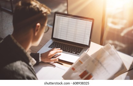 Young banking finance analyst in eyeglasses working at sunny office on laptop while sitting at wooden table.Businessman analyze stock reports on notebook screen.Blurred background,horizontal