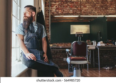 Young barber at his barbershop. Caucasian male with long beard sitting on sill of a window and looking outside.