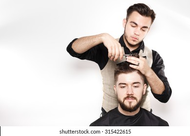 Young barber, wearing in black shirt, with scissors and black comb, cuts hair on head of brunette bearded client, on white background in studio, waist up