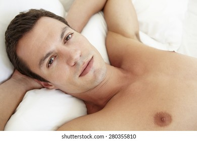Young Bare Chested Man Relaxing On Bed