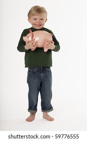 A young, barefoot boy is standing and smiling while holding a piggy bank. Vertical shot.