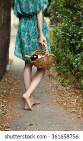 Young barefoot girl holding straw basket with a bottle of wine over natural background