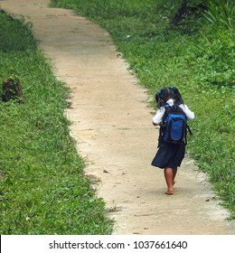 Young barefoot  indigenous girl in a school uniform walking along a government built cement community path.  Location is on a remote island off the Caribbean coast of Panama south of Bocas del Toro