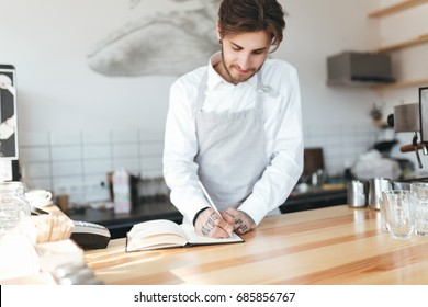 Young barista in apron and white shirt writing in notebook on workplace at counter in restaurant. Barista thoughtfully making notes at work in coffee shop. Portrait of young barista on workplace