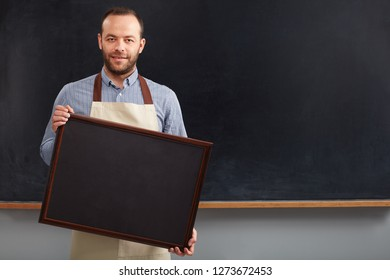 Young barista holding placard front blackboard.