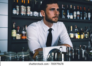 young barista male in the workplace behind the bar