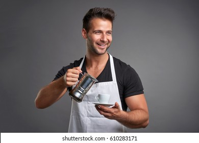 A young barista man smiling and pouring coffee from a percolator to a coffeecup