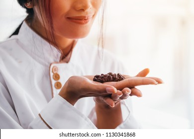Young barista smelling coffee beans on her palm of hands with smile with copy space